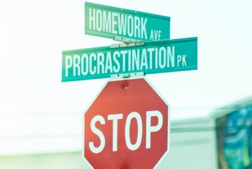 Street signs labelled homework and procrastination atop a red stop sign