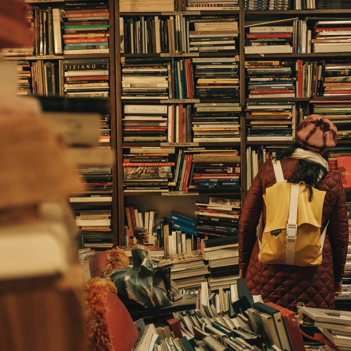 Woman with backpack looking at books on jumbled shelves
