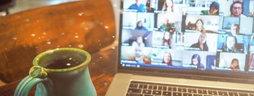A ceramic turquoise mug sits next to a computer showing a virtual conference on the screen
