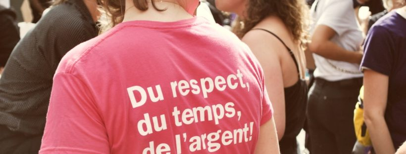 Woman wearing a pink t-shirt with white printed text: Du respect, du temps, de l'argent